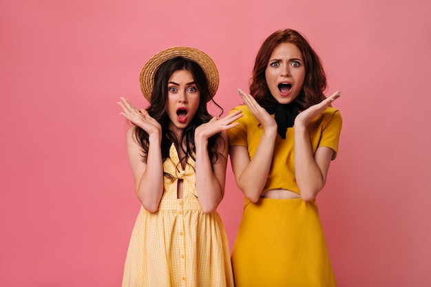 Garotas surpresas em roupas amarelas posando na parede rosa