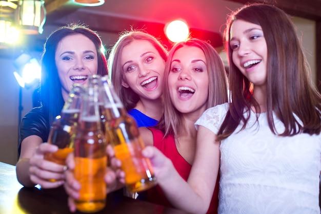 Garotas tilintam copos de cerveja no clube.