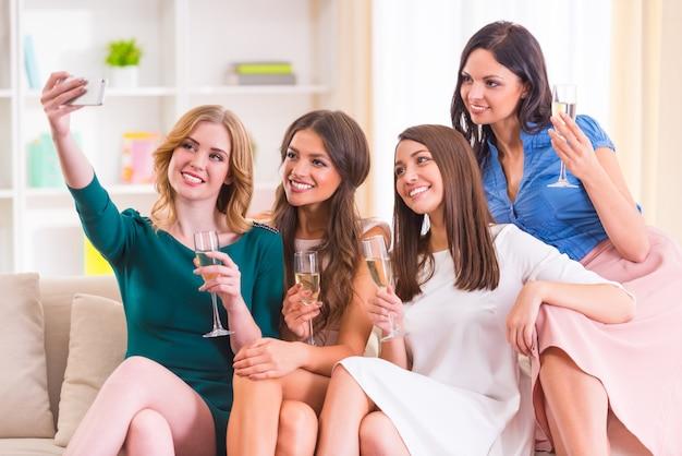 Garotas tiram selfies e bebem champanhe em casa.