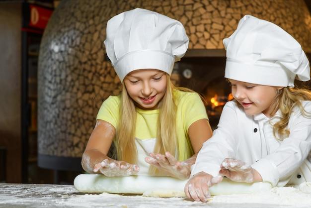 Garotas vestidas de cozinheira fazendo massa