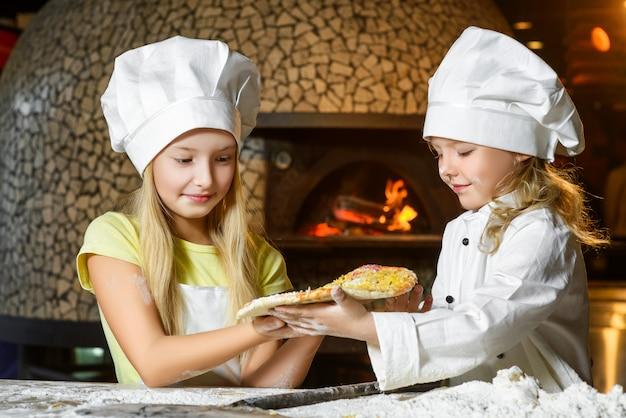 Garotas vestidas de cozinheira preparando pizza