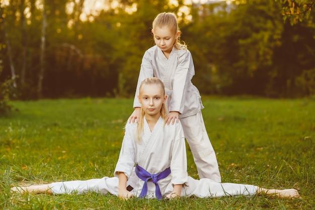 Garotas vestidas de quimono fazendo exercícios de caratê