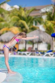Garotinha adorável ativa na piscina ao ar livre pronta para nadar