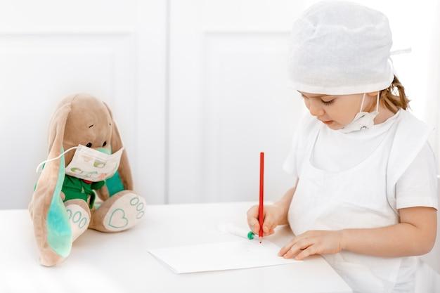 Garotinha adorável com máscara médica, brincando de médico, preenche o formulário de prescrição para o paciente