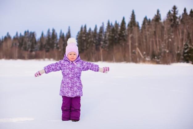 Garotinha adorável desfrutando de neve dia ensolarado de inverno