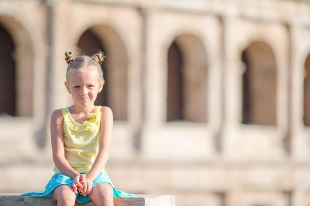 Garotinha adorável na frente do coliseu, em roma, itália