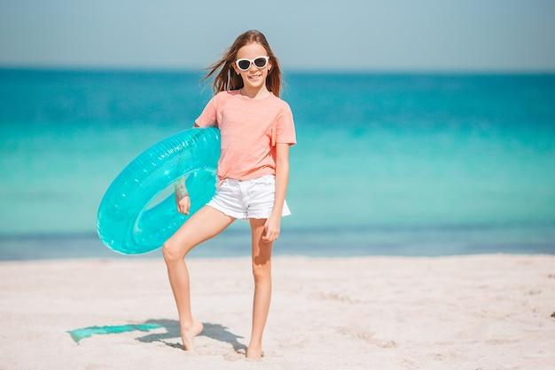 Garotinha adorável se divertindo em uma praia tropical durante as férias