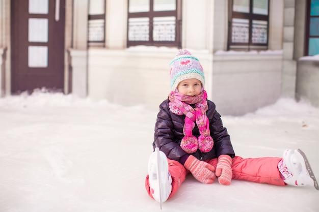 Garotinha adorável sentado no gelo após a queda