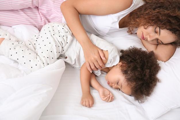 Garotinha afro-americana com a mãe dormindo na cama