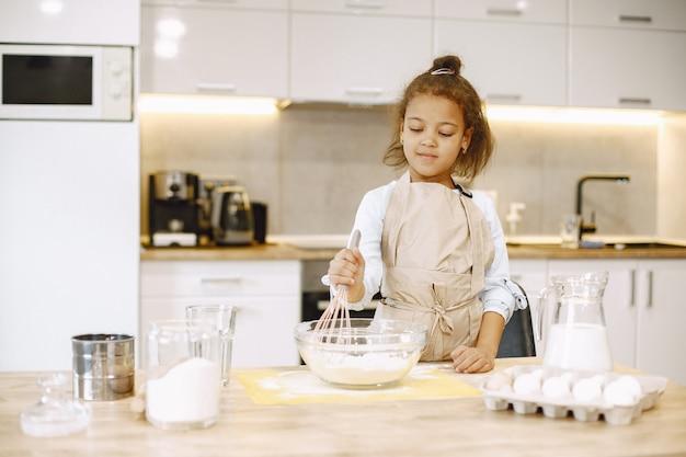 Garotinha afro-americana, misturando a massa em uma tigela de vidro, preparando um bolo.