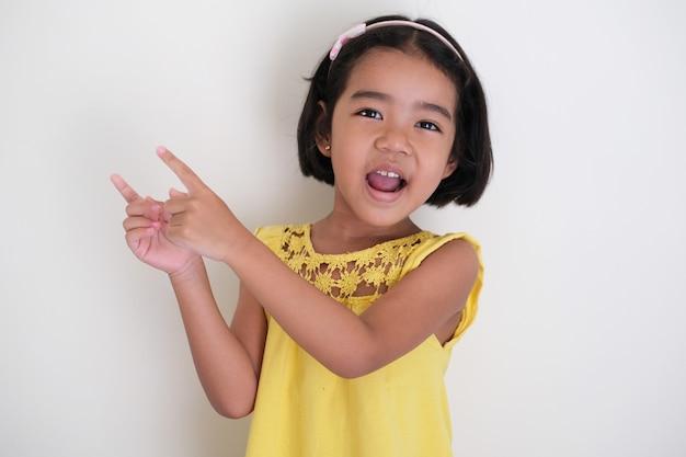 Garotinha asiática apontando o dedo ao lado com uma expressão de rosto feliz
