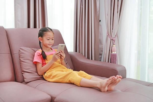 Garotinha asiática bonitinha brincando de smartphone no sofá da sala de estar em casa