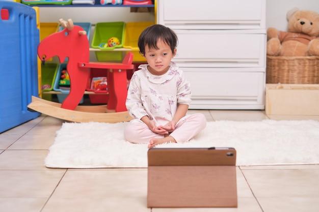 Garotinha asiática de 2 anos de idade pratica ioga e medita com treinamento online em um tablet em casa, meditação para iniciantes, exercícios respiratórios para crianças