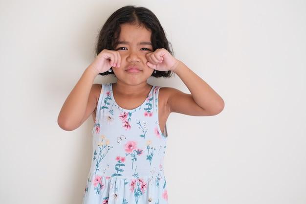 Garotinha asiática em gesto de choro isolado no branco
