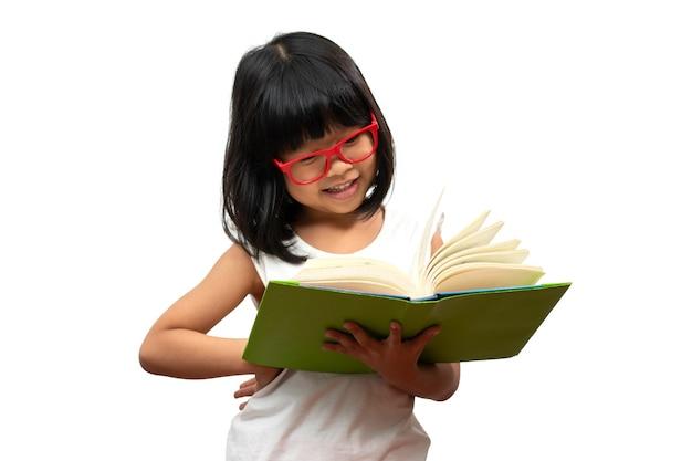Garotinha asiática feliz em idade pré-escolar usando óculos vermelhos, segurando e lendo um livro verde