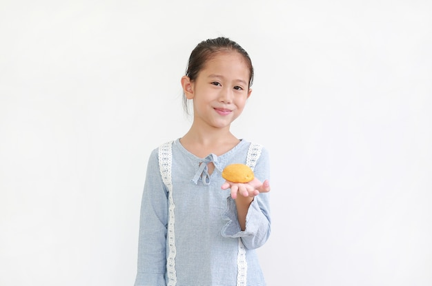 Garotinha asiática feliz segurando e comendo bolo de creme isolado sobre o branco