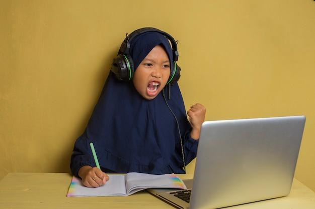 Garotinha asiática muçulmana feliz usando seu laptop