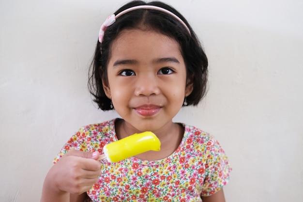 Garotinha asiática sorrindo enquanto segura um sorvete amarelo