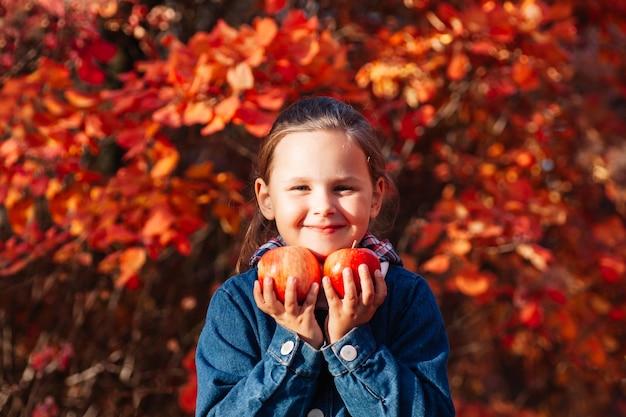 Garotinha bonita com casaco jeans e conceito de parque outono segurando uma grande maçã vermelha com fundo de outono