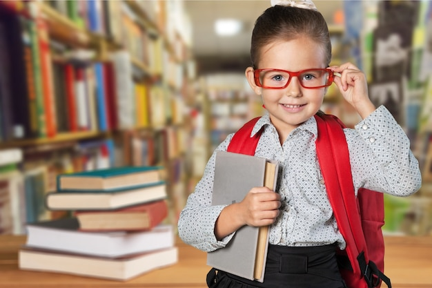 Garotinha bonitinha de óculos com livros no fundo