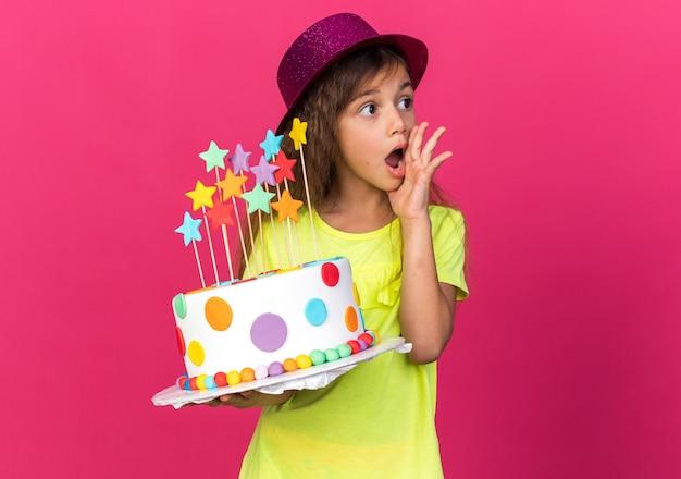 Garotinha caucasiana chocada com chapéu de festa roxo, colocando a mão no rosto e segurando um bolo de aniversário, olhando para o lado isolado na parede rosa com espaço de cópia