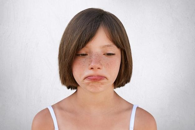 Garotinha chateada, com pele sardenta e cabelos cortados, curvando os lábios com uma expressão triste, infeliz ao descobrir que os pais não compraram seu brinquedo. menina bonita sardenta vai chorar