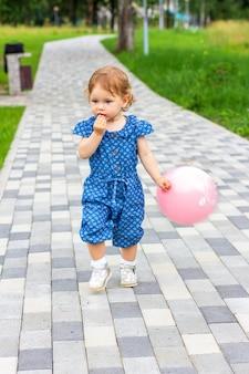 Garotinha com um balão rosa na mão corre ao longo de um caminho em um parque de verão