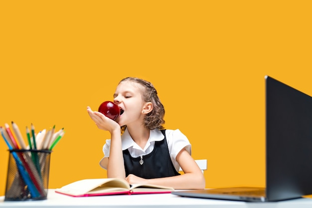 Garotinha comendo uma maçã enquanto troca de roupa em uma aula online de educação a distância