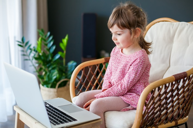 Garotinha conversando por vídeo com os avós usando um laptop