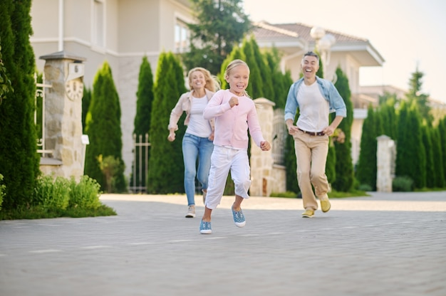 Garotinha correndo alegre e conversando com os pais