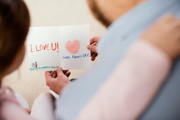 Garotinha dando um cartão para o pai no dia dos pais