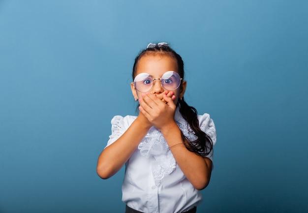 Garotinha de colegial de óculos cobriu a boca com as mãos. conceito de crianças e emoções.