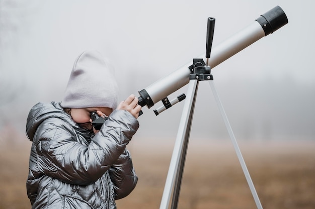 Garotinha de lado usando um telescópio