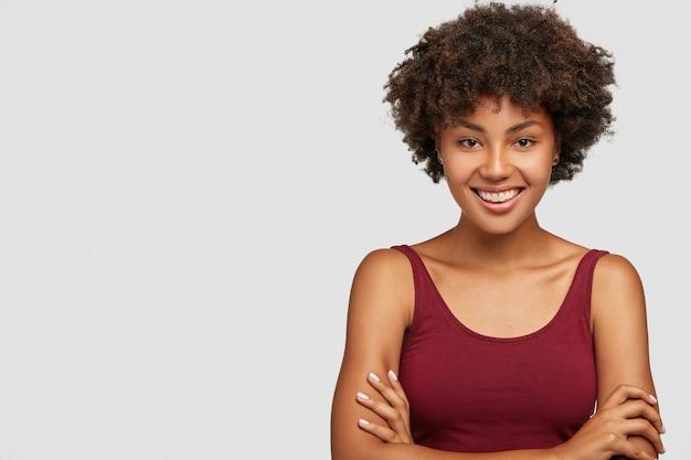 Garotinha de pele escura, de aparência amigável e autoconfiante mantém os braços cruzados