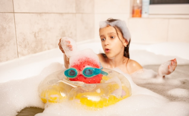 Garotinha divertida se banhando em uma banheira de espuma e jogando bola salva-vidas