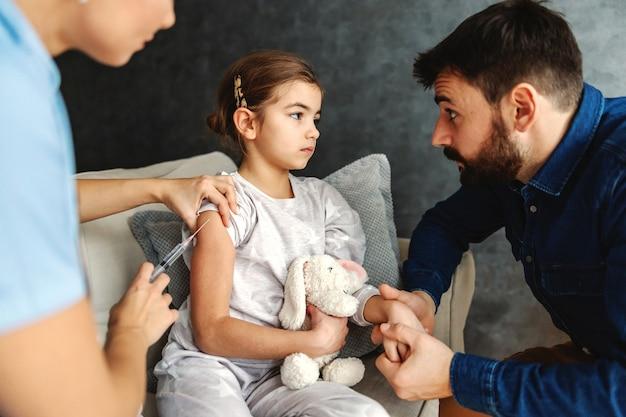 Garotinha doente recebendo uma injeção com cura