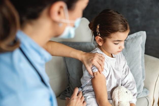 Garotinha doente sentada no sofá em casa tomando injeção durante um surto secreto