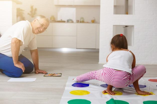 Garotinha e avô brincam de twister em casa