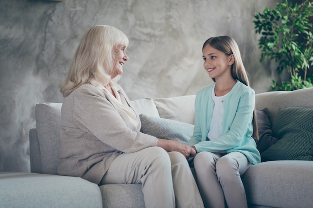Garotinha e avó sentadas no sofá