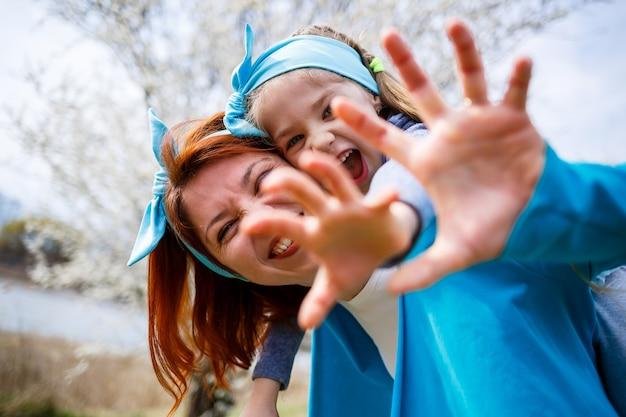 Garotinha e mãe mulher caminham pela floresta de primavera com árvores floridas, riem e brincam, o início da primavera, férias em família, amor dos pais