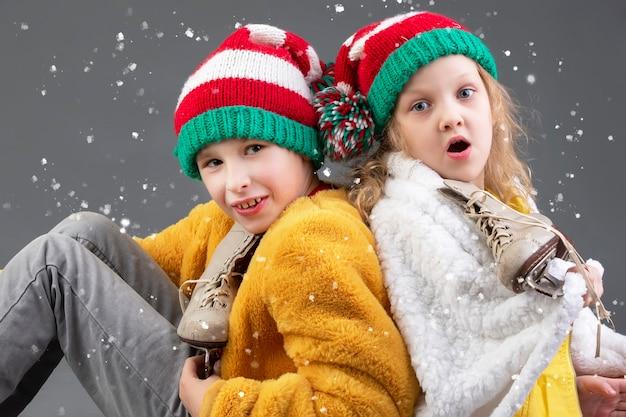 Garotinha e menino engraçados com chapéus de natal tricotados e patins de gelo vintage. crianças feliz natal