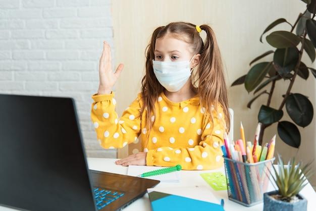 Garotinha em casa, aprendendo aula virtual on-line sobre internet com um professor por reunião remota devido à pandemia covid-19, levantando a mão