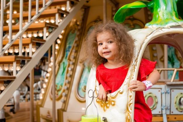 Garotinha encaracolada em uma carruagem como uma princesa da cinderela.