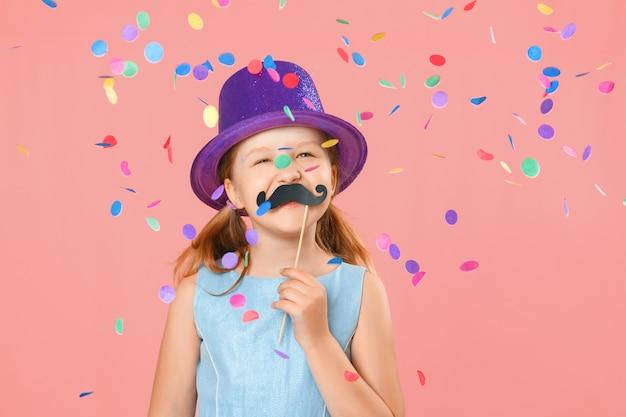 Garotinha engraçada com bigode falso e usando um chapéu sob os confetes caindo.