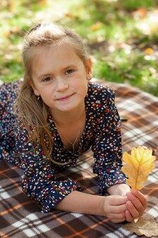 Garotinha engraçada encontra-se nas folhas amarelas na floresta. criança em uma caminhada no parque outono. menina pré-escolar na rua.