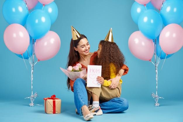 Garotinha engraçada parabeniza sua mãe, fundo azul. a criança bonita abraça a mãe, celebração de evento ou festa de aniversário, balões e decoração de caixa de presente