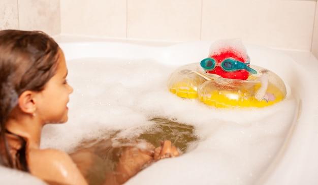 Garotinha engraçada se banhando em uma banheira de espuma e jogando bola salva-vidas e óculos de natação