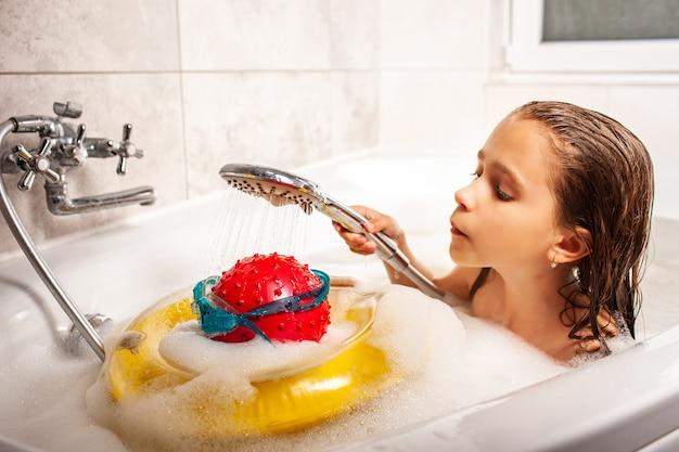 Garotinha engraçada tomando banho com uma cabeça feita de bola e óculos de natação