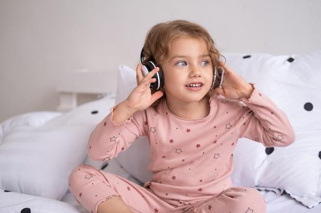 Garotinha feliz sorridente de pijama com fones de ouvido sem fio ouvindo música na cama em casa