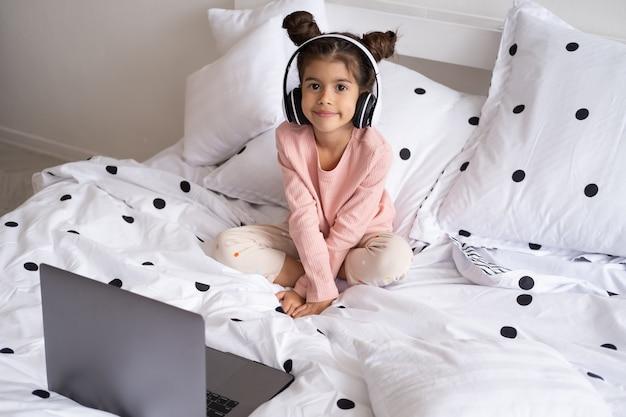 Garotinha feliz sorridente usando laptop em fones de ouvido sem fio na cama em casa